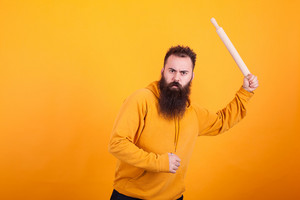 Bearded man using paddle as if was a baseball bat over yellow background. Agressive expression.