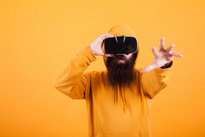 Bearded man wearing virtual reality headset reaching out with his hand over yellow background. Yellow hoodie. Handsome man. Hipster man.