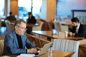 Bearded mature entrepreneur wearing eyeglasses writing email to his business partner on modern laptop while sitting in spacious cafe, waist-up portrait