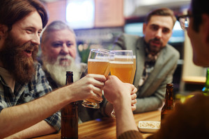 Bearded men with glasses of beer toasting during hangout