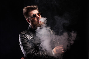Bearded rocker with stylish glasses over black background. Attractive man. Leather jacket. Cigarette smoke.