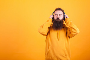 Bearded young man wearing yellow hoodie ,listening music on his blue headphones peacefully over yellow background. Handsome man. Great song.
