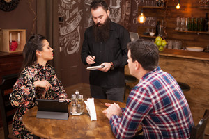 Bearded young waiter taking the order from young couple in restaurant. Vintage pub.