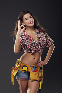 Beautiful and sexy female construction worker gesturing OK sign