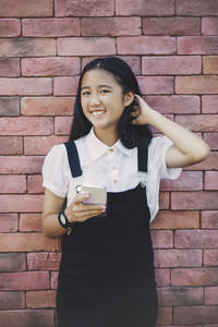 beautiful asian teenager toothy smiling face using smarphone in hand