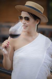 beautiful asian woman drinking red wine in wine glass