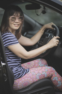 beautiful asian woman sitting on car driver seat toothy smiling face