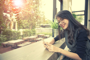 beautiful asian younger woman laughing with happiness emotion reading smart phone