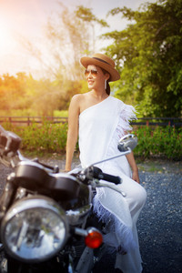 beautiful asian younger woman riding on vintage motorcycle