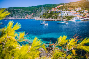 Beautiful Assos village, Kefalonia. Greece. White cruise yachts staying at anchor in beautiful emerald green colored lagoon water. Framed by pine trees branch