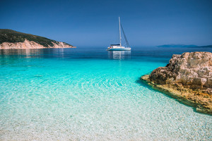 Beautiful azure blue lagoon with sailing catamaran yacht boat at anchor. Pure white pebble beach, some rocks in the sea
