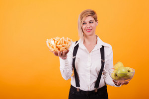 Beautiful blond woman with short hair balancing two bowls over yellow background. Corn puffs. Green apples.