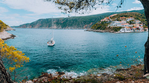 Beautiful blue bay surrounded by mountains in Assos village located on Kefalonia. Summer tourism vacation sailing boat trip around Greece