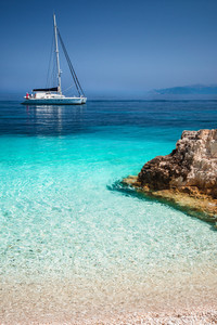 Beautiful calm azure blue lagoon with sailing catamaran yacht boat at anchor. Pure white pebble beach with rocks in the sea