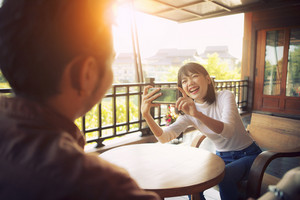 beautiful cheerful asian younger woman taking a photo by smart phone with happiness emotion