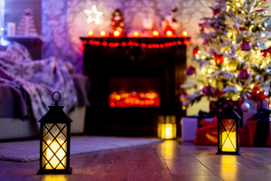 Beautiful Christmas background with burning candles and fireplace. Christmas night.