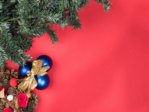 Beautiful Christmas wreath with christmas tree and globes on red background. Holiday mood.