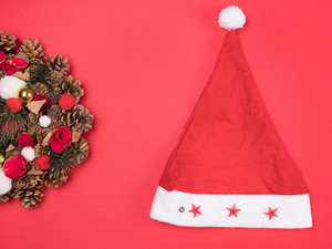 Beautiful Christmas wreath with santa hat on red background. Festive interior decor.