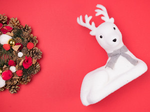 Beautiful Christmas wreath with white reindeer toy on red background. Festive interior decor