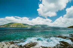 Beautiful cloudscape near Fiskardo, Kefalonia, Ionian islands, Greece. Crystal clear transparent blue turquoise teal Mediterranean sea water in Fiskardo town. White catamaran yacht drift in open sea