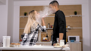 Beautiful couple having fun while cooking their romantic dinner. Strong conection