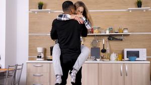 Beautiful couple joking around while cooking dinner. Having fun