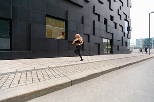 Beautiful fast running woman wearing sports top in modern city environment