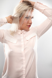 Beautiful female blonde model in pink shirt holding her hair