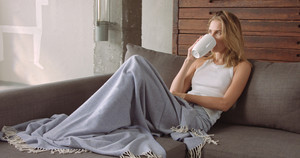 Beautiful female model on a couch with a cup of coffee under a blue blanket looking at the camera and then going back to her thoughts.