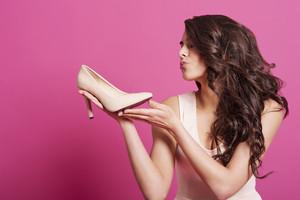 Beautiful female shopaholic kissing high heels
