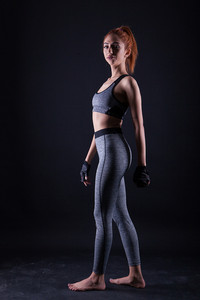 Beautiful fitness young woman doing lateral pose during studio photoshoot on black background. . Powerfull girl .