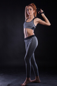 Beautiful fitness young woman doing lateral pose during studio photoshoot on black background. Powerfull girl.