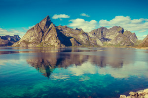 Beautiful fjord in Lofoten. Beautiful nature with blue sky, reflection in water, rocky beach . Lofoten islands, Reine, Norway