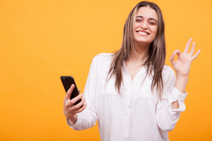 Beautiful girl in white shirt holding phone and showing ok sign over yellow background. Hand gesture