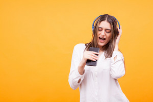 Beautiful girl singing and listening music on her headphones over yellow background. Party time