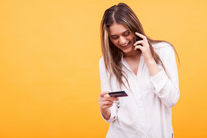 Beautiful girl smiling while talking on the phone and holding credit card over yellow background. Happy conversation