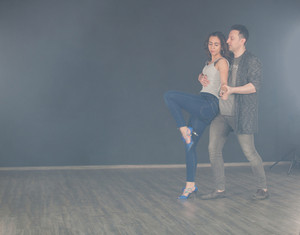 Beautiful kizomba dancer doing walking steps while her partner pickes her up. Caucasian woman.