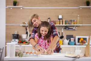 Beautiful little girl helping her mother prepare some cookies at home. Enjoying cooking.