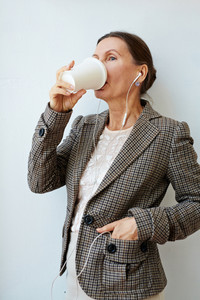 Beautiful mature entrepreneur standing against white wall with headphones in ears, drinking delicious coffee from paper cup and looking away, portrait shot