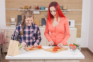 Beautiful mother and daughter slicing tomatoes for tasty salad. Preparing food.