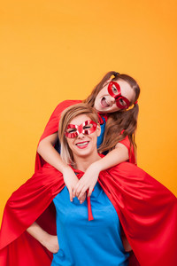 Beautiful mother and her cute little girl dressed like heroins playing together over yellow background. Little girl having fun. Mother and daughter bonding.