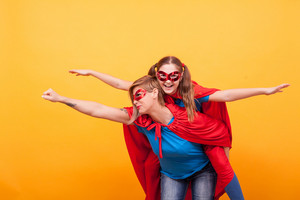Beautiful mother and her cute little girl playing together dressed like superheros over yellow background. Good parenting. Happy kid. Mother and daughter bonding.