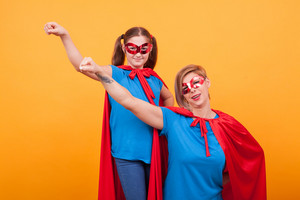 Beautiful mother and her little daughter dressed like superheros are keeping one hand up over yellow background. Looking and smiling to the camera. Great motherhood. Happy kid.