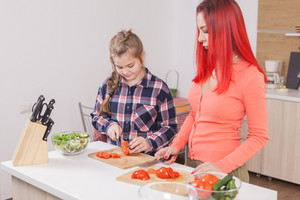 Beautiful mother slicing tomatoes for salad. Smiling at her daughter.