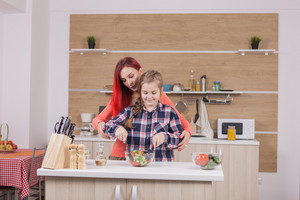 Beautiful mother with her daughter cooking tasty food. Healthy lifestyle