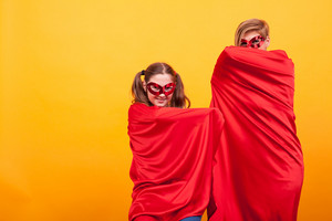 Beautiful mother with her daughter dressed like superheros hiding under their red cape over yellow background. Red mask. Good parenting.