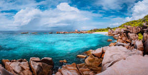 Beautiful panorama with impressive white fluffy clouds wild rocky beach Anse Marron in Seychelles. La Digue