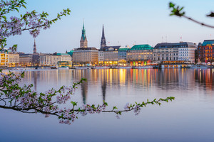 Beautiful panoramic view of calm Alster river with Hamburg town hall - Rathaus behind the buildings on evening. Golden hour with cherry blossom tree in foreground