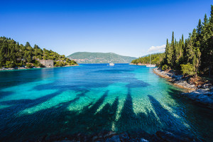 Beautiful Phoki Beach surrounded by cypress trees in the evening sunlight. Amazing seascape of Ionian Sea. Cypress shadows on the clear azure water. Greece
