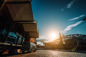 Beautiful retro style car packed on the cobbled square. Arch bridge over canals with Sankt Katherinen church in the background. Warehouse district in Hamburg, Germany. Warm sunset light. Revival style